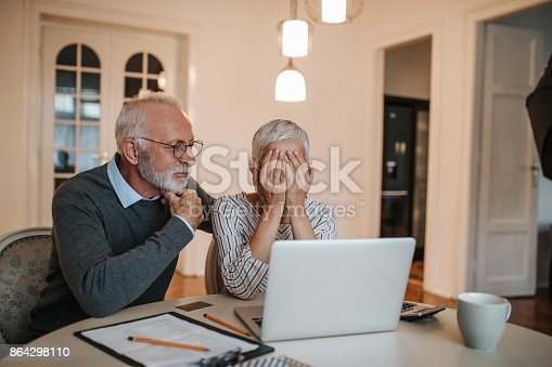 A senior husband comforting his wife as they are looking into their finances.