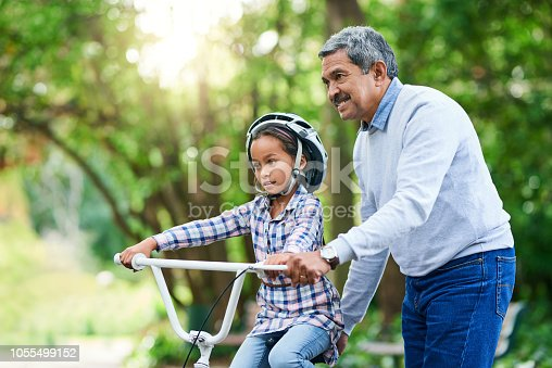 Cropped shot of an adorable little girl learning how to ride a bike while enjoying the day outdoors with her granddad