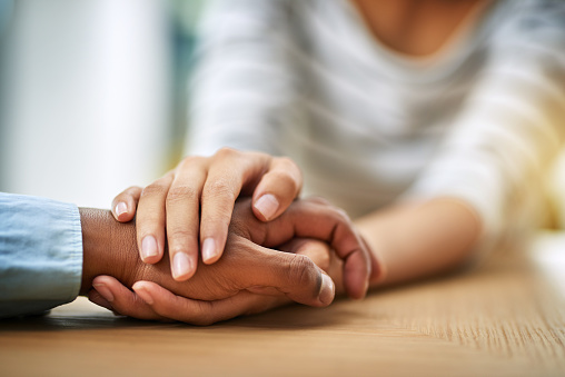 Cropped shot of two unrecognizable people holding hands while being seated at a table inside during the day