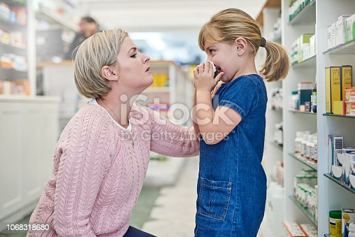 Shot of a young woman looking concerned about her sick little daughter in a pharmacy