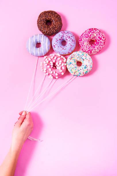 donut-ballons halten durch die hand einer frau. - löcherkuchen stock-fotos und bilder