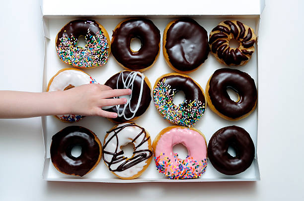 Donut Box with Young Girl's Hand Grabbing One stock photo
