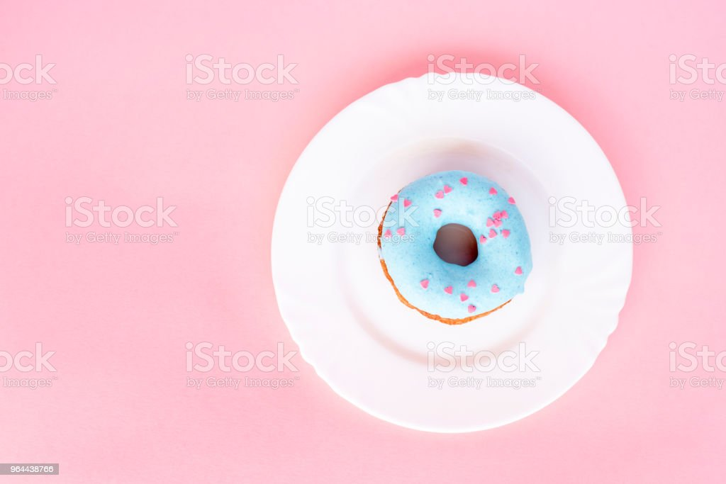 Donut covered with blue glaze and sprinkled with small pink roundels on white plate - Royalty-free Baked Stock Photo