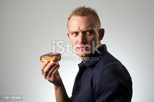 Studio Portrait of a young Caucasian male against a white background with a donut South Africa