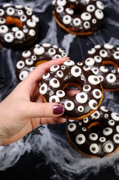 donut für halloween - schokolade gebratene kuchen stock-fotos und bilder