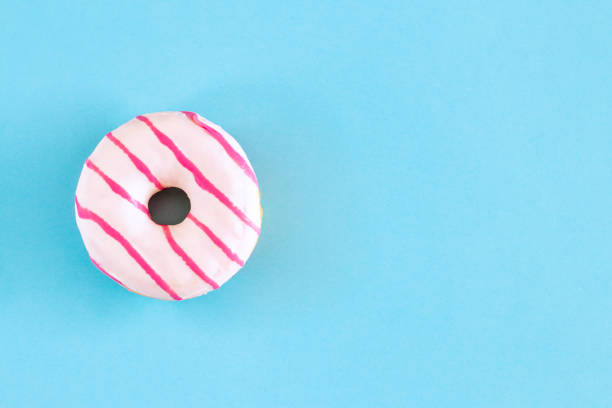 donut on blue background and copy space - bombolone foto e immagini stock