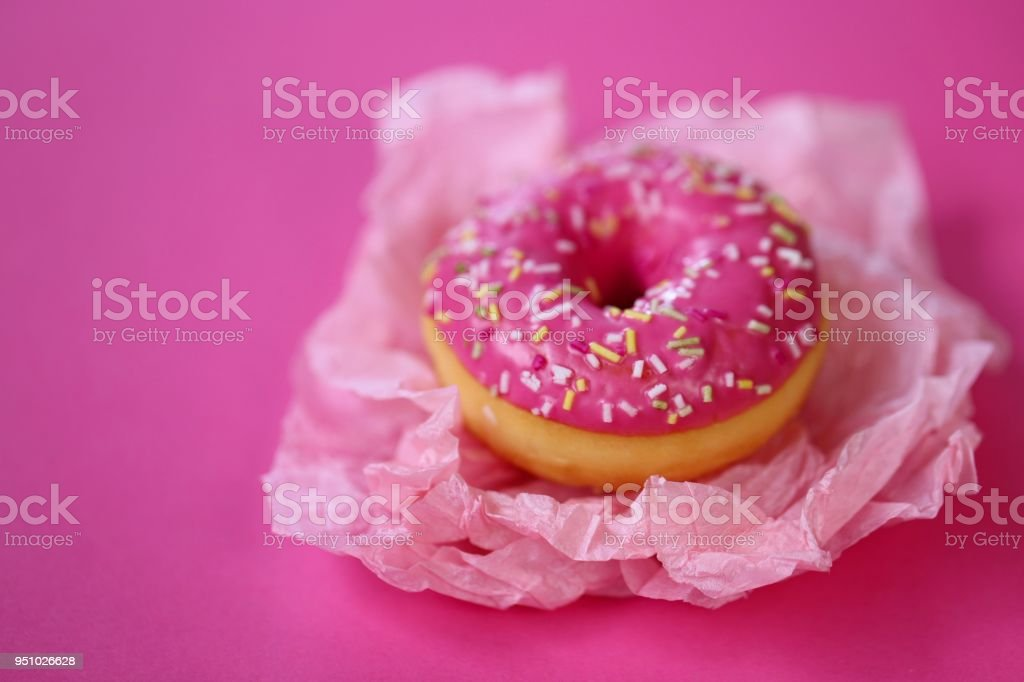Donut. pink donut on a light pink crumpled paper on a bright fuchsia background. Appetizing dessert stock photo