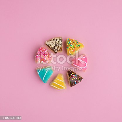 istock Donut shape made of cut donut slices on pink background. 1157606190