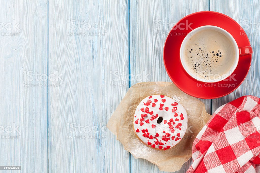 Donut with heart shaped decor and coffee stock photo