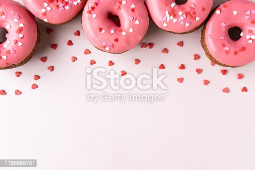 Donut with heart shaped decor on pink background. Top view with copy space