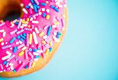 ドーナツにピンクのクリームと光り輝く青を背景にした