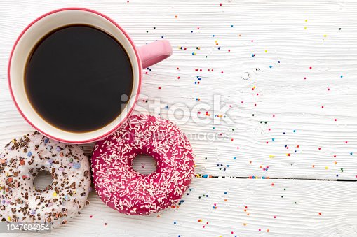 coffee and donuts on wooden table. Top View