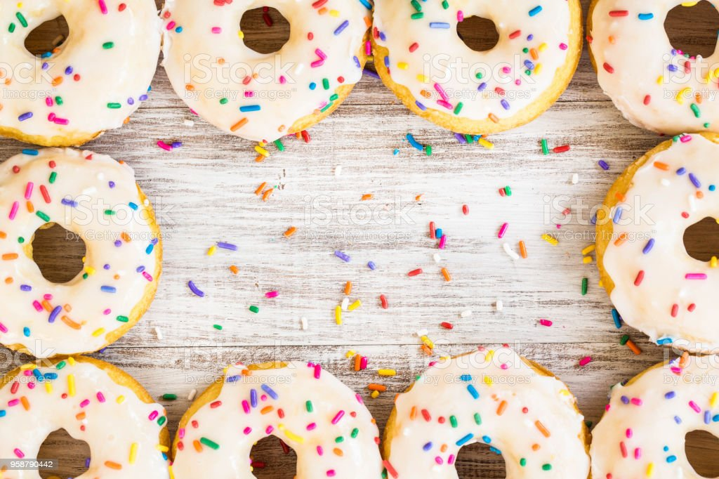 Donuts Arranged On White Wood Background With Sprinkles stock photo