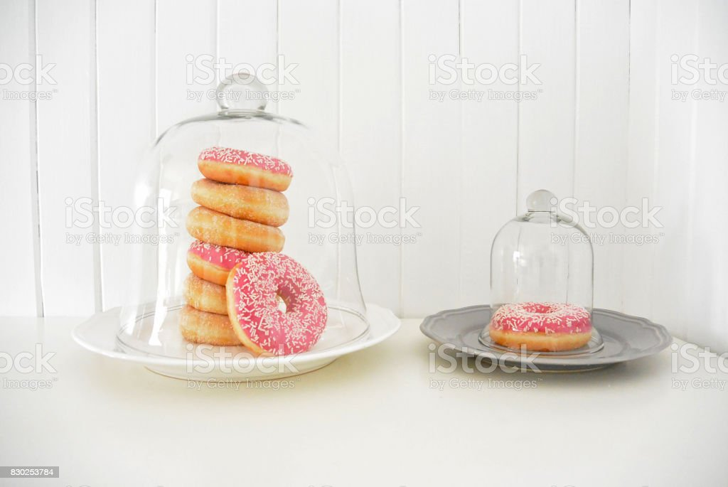 Donuts covered glass bell Wooden planks background stock photo