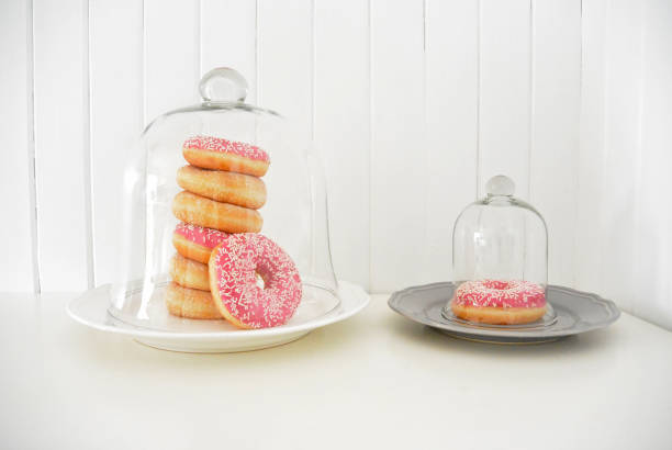 donuts covered glass bell wooden planks background - big cake stock photos and pictures