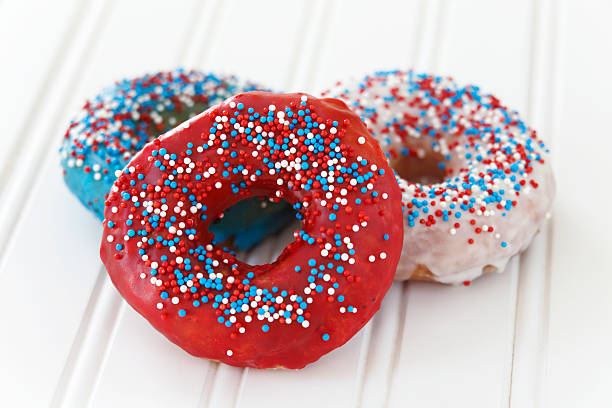 Donuts decorated with icing and sprinkles stock photo
