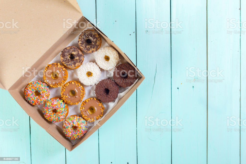 Donuts in box on wooden table. stock photo