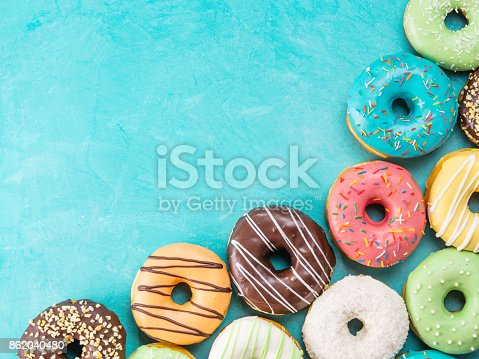 istock donuts on blue background , copy space, top view 862040480
