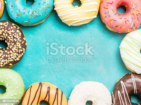 862040870istockphoto donuts on blue background , copy space, top view 862040640