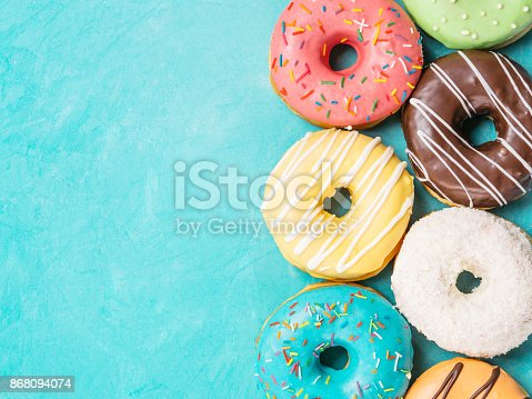 istock donuts on blue background , copy space, top view 868094074