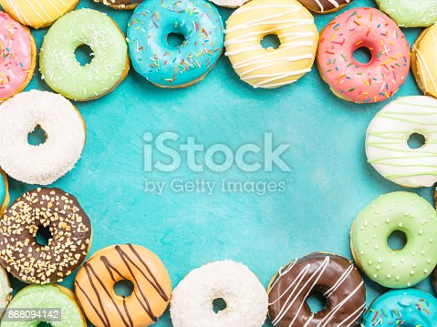 istock donuts on blue background , copy space, top view 868094142