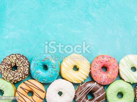 862040870istockphoto donuts on blue background , copy space, top view 912109010