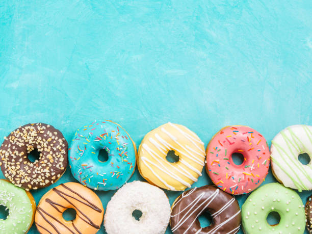 donuts on blue background , copy space, top view - bombolone foto e immagini stock