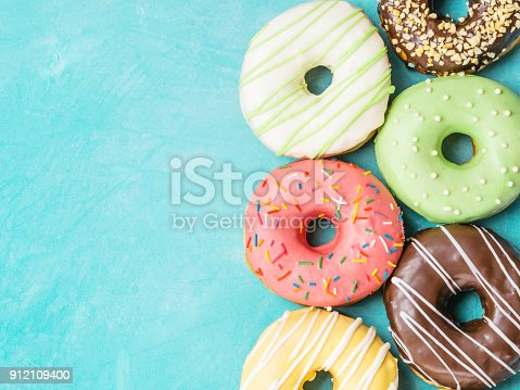 862040870istockphoto donuts on blue background , copy space, top view 912109400