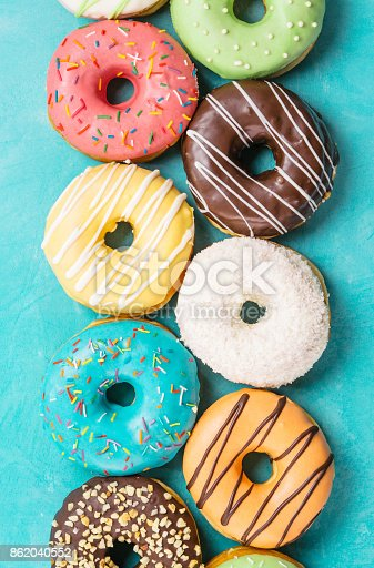 istock donuts on blue background, top view 862040552