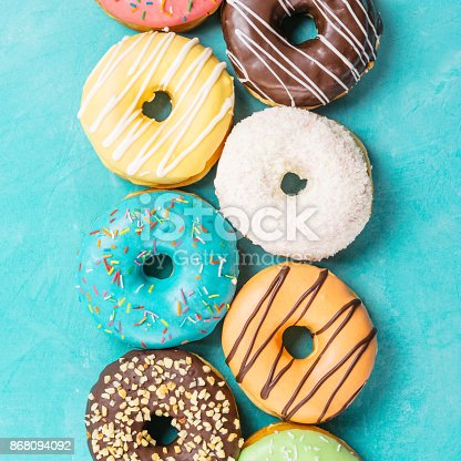 istock donuts on blue background, top view 868094092
