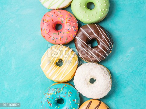 istock donuts on blue background, top view 912109524