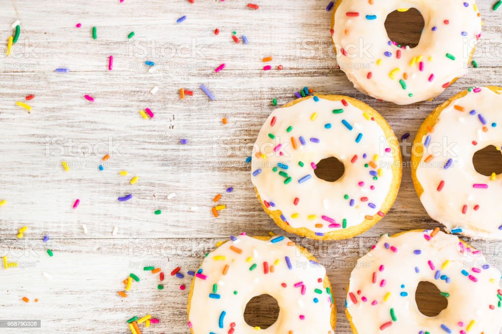 Donuts on White Wood Background With Sprinkles stock photo