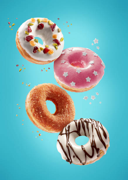donuts selection flying on blue background. various doughnuts isolated on colorful background - bombolone foto e immagini stock