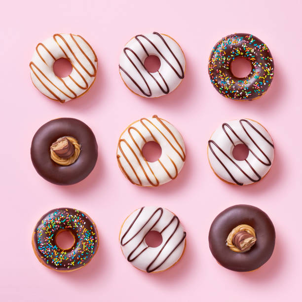donuts selection on a light pink background viewed from above. top view - bombolone foto e immagini stock