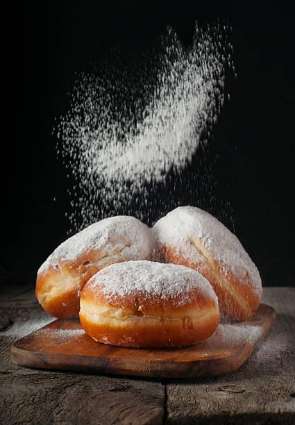 donuts mit puderzucker bestreut - hausgemachte gebackene donuts stock-fotos und bilder