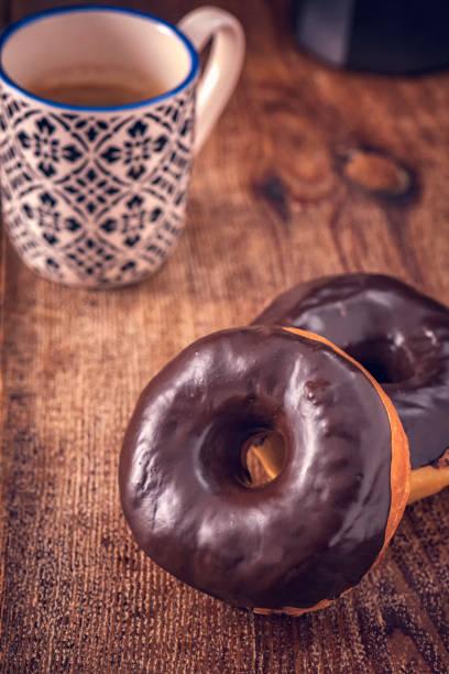 donuts mit schokolade - deutscher schokoladen zuckerguss stock-fotos und bilder