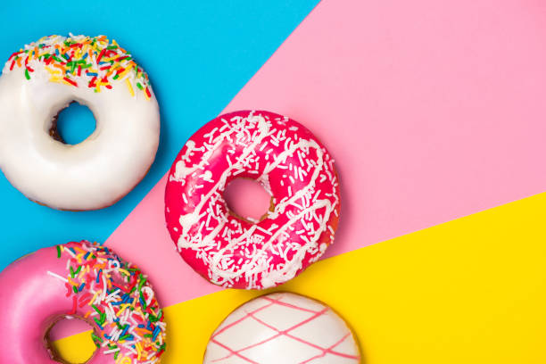 Donuts with icing on colorblock background. Sweet donuts. stock photo