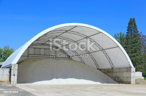 A doom shelter building made with a canvas material is used to store rock salt for icy conditions on the roadway