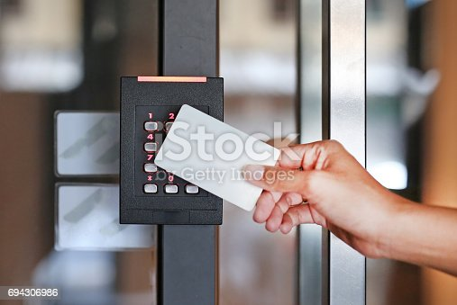 istock Door access control - young woman holding a key card to lock and unlock door. 694306986