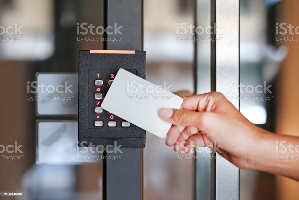 Door access control - young woman holding a key card to lock and unlock door. stock photo