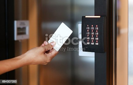 istock Door access control - young woman holding a key card to lock and unlock door. 694307000