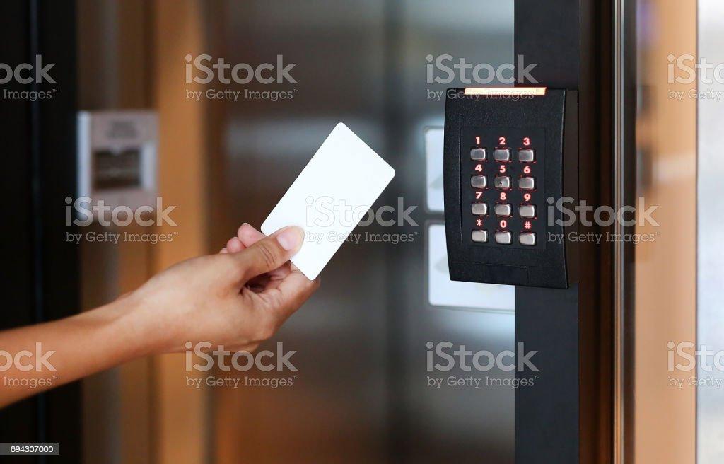 Controle de acesso de porta - jovem mulher segurando um cartão-chave para bloquear e desbloquear a porta. - foto de acervo