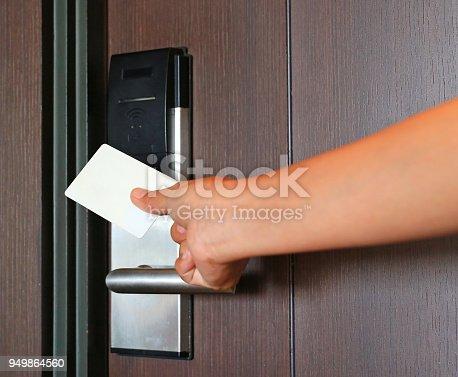 istock Door access control - young woman holding a key card to unlock door. 949864560