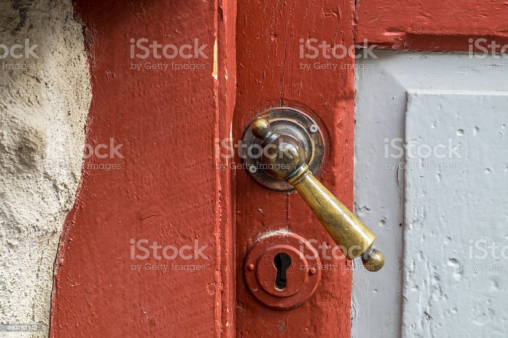 Door handle Red wooden door in Røros, Unesco mining town.  Aging Process Stock Photo