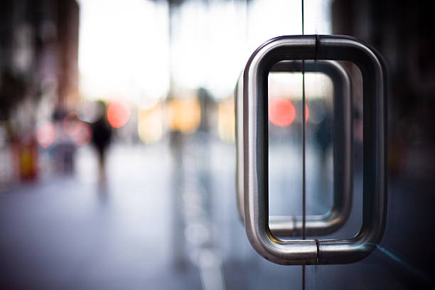 door handles on a glass office building - building entrance stock photos and pictures