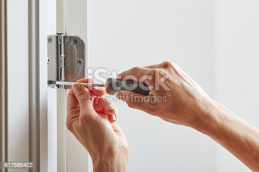 Hands with screwdriver fixing a door hinge.
