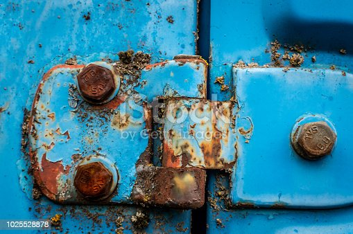 Door hinge of a blue car rusted nuts abandoned