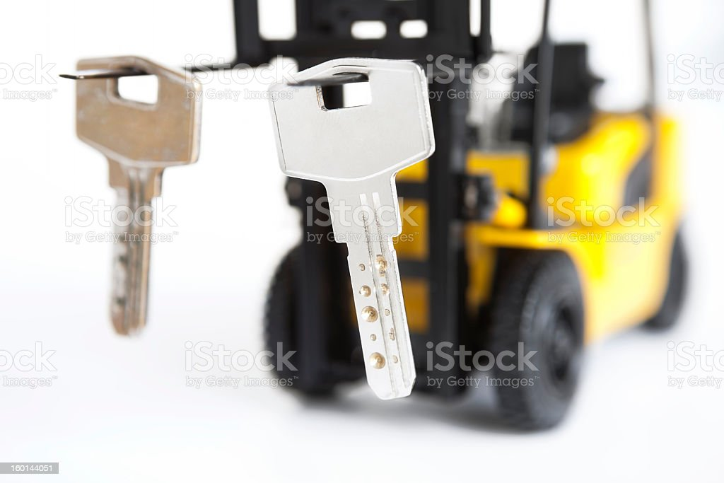 door key hanging from the tip of a toy forklift stock photo