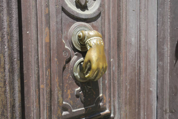 deurklopper, koperen hand met ornamenten op een bruine houten deur foto