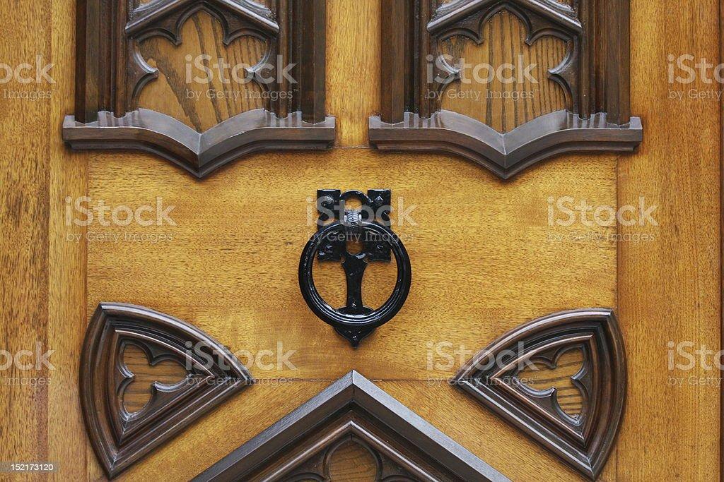 Door Knocker An ornate knocker on a vintage wooden door. Brass Stock Photo